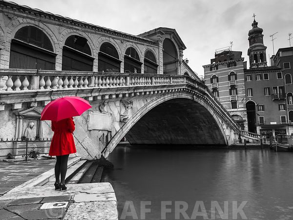 A woman in a red dress holding red umbrella and standing next to the Rialto bridge, Venice, Italy