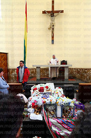 Priest giving mass in church with skulls in front of altar, Ñatitas festival, La Paz, Bolivia