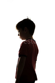 A silhouette of a boy standing in a t-shirt - shot from low level.