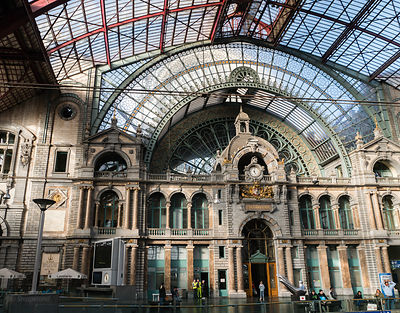 2018-10-01 Antwerp, Belgium: Richtly decoratedt train hall of Antwerp Central Station with passengers and clock