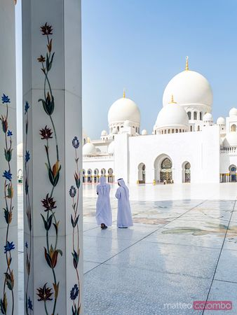 Arabic men walking inside Grand Mosque, Abu Dhabi, UAE