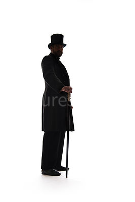 A Victorian man in a hat and coat, standing with a cane, in silhouette – shot from low level.