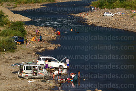 Families washing vehicles and playing in river near Caranavi, Bolivia
