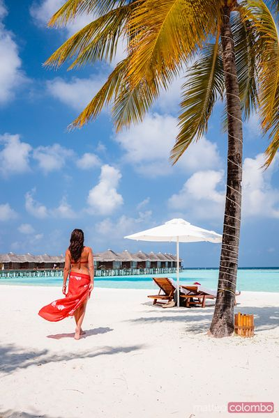 Woman standing near palm tree in the Maldives