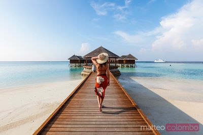 Woman walking on jetty in a resort, Maldives
