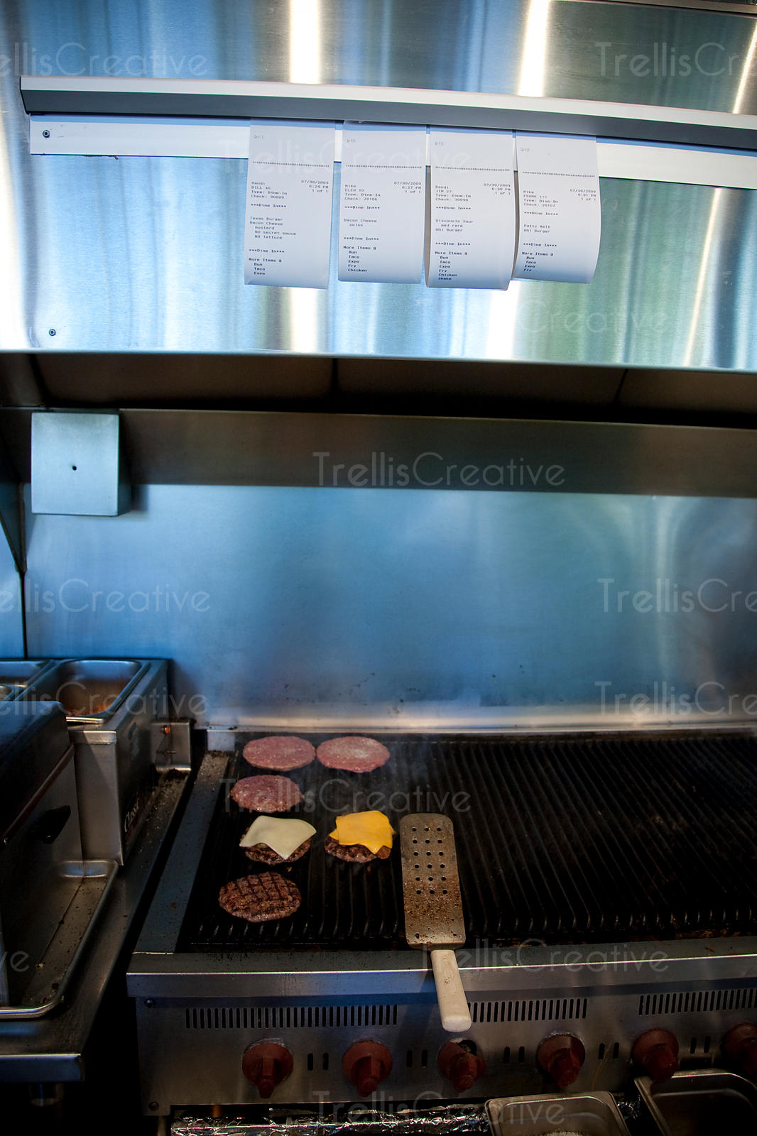 Cooking hamburgers over open flame grill