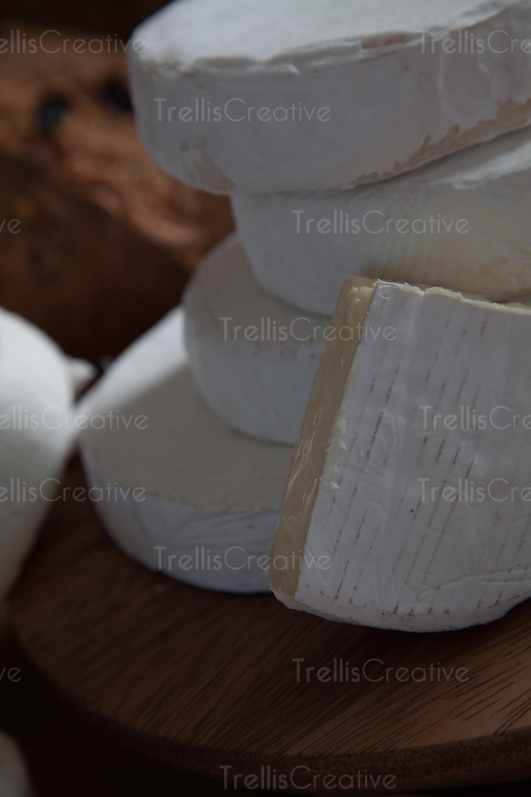 Close-up of stacks of brie cheese and a wedge on a wooden cheese board
