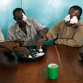 Patients have breakfast before the doctor takes off their bandages after their surgery. Double cataract patient Chansa Lloyd ...