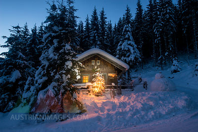 Austria, Altenmarkt-Zauchensee, sledges, snowman and Christmas tree at illuminated wooden house in snow at night