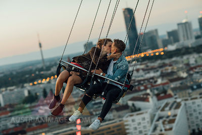 Young couple in love, riding chairoplane on a fairground