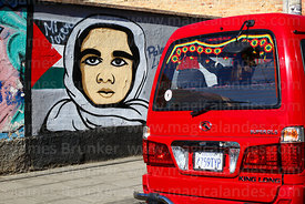 Minibus with rosettes in colours of Bolivian flag on rear window driving past mural showing support for Palestine, La Paz, Bo...