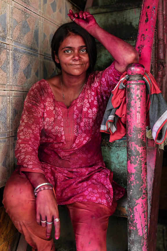 A Woman Stained with Holi Color Sits at the Entrance to a Shop
