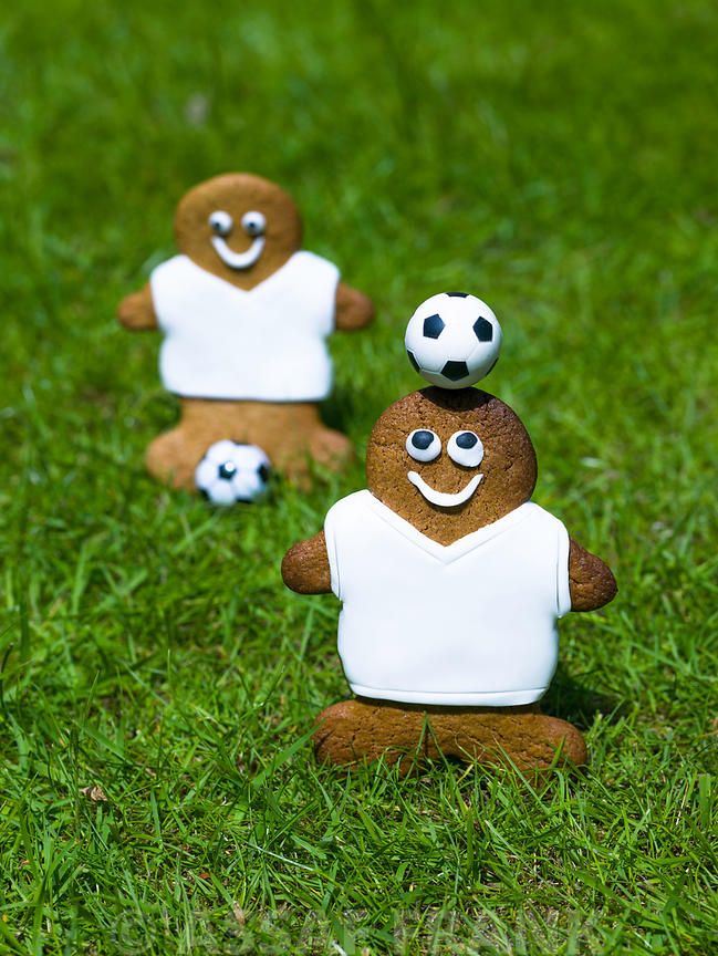 Pair of gingerbread footballers with football on grass