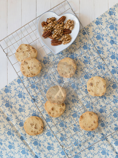 Maple, Walnut and Pecan Cookies on a baking tray, nuts in a heart shaped bowl.