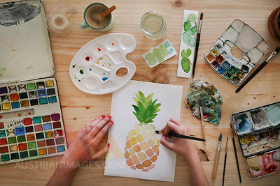 Woman's hand painting aquarelle of a pineapple on desk in her studio