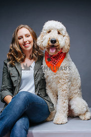Caucasian woman and her dog in a studio portrait.