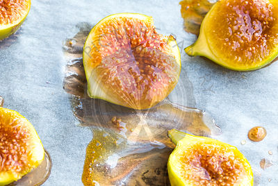 oven roasted green figs on baking paper showing drizzled honey