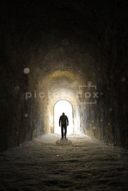An atmospheric image of the silhouette of a lone mystery walking towards the light in a dusty old tunnel.