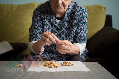 Aged woman eating pistachios at home
