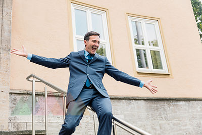 Carefree businessman sliding down railing in the city