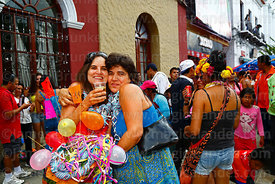 A woman with her friend / comadre after giving her a decorated basket during the Comadres festival, Tarija, Bolivia