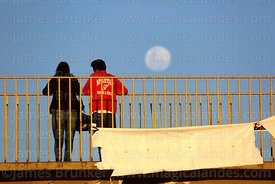 Young couple on footbridge watching the full moon rising, El Alto, Bolivia
