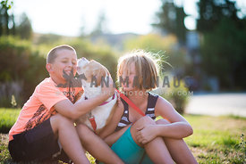 Happy pitbull mix kissing young children