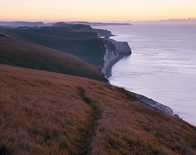 Dawn arrives on the Jurassic Heritage Coast of Dorset. Viewed from this clifftop the steeply undulating chalky cliffs of the ...