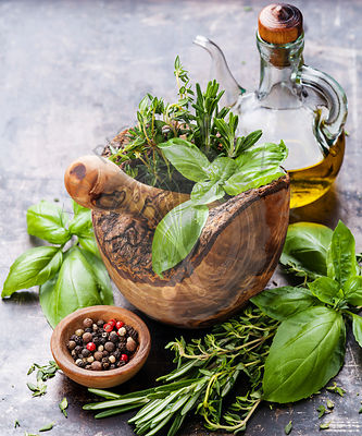 Fresh spicy herbs in olive wood Mortar on dark background