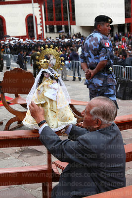 Devotee adjusts robe of his Virgen de la Candelaria statue before central mass, Puno, Peru
