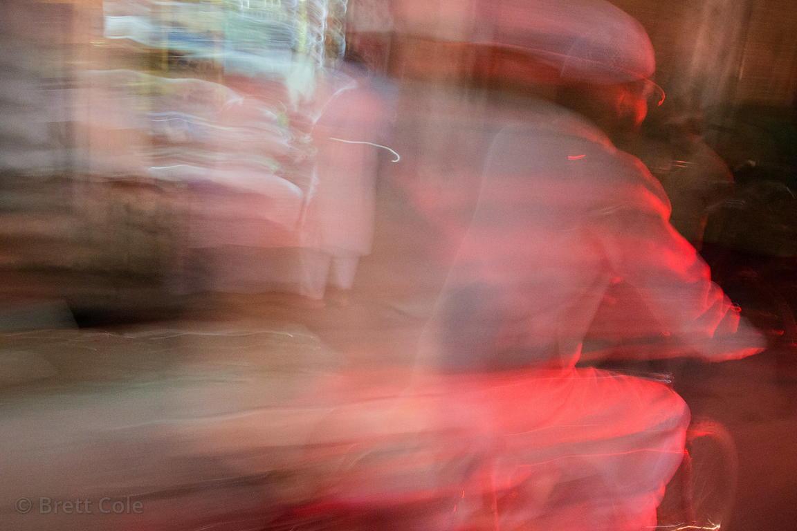 Long exposure of a Muslim man passing by at night on a bicycle, Bangali Tola, Varanasi, India