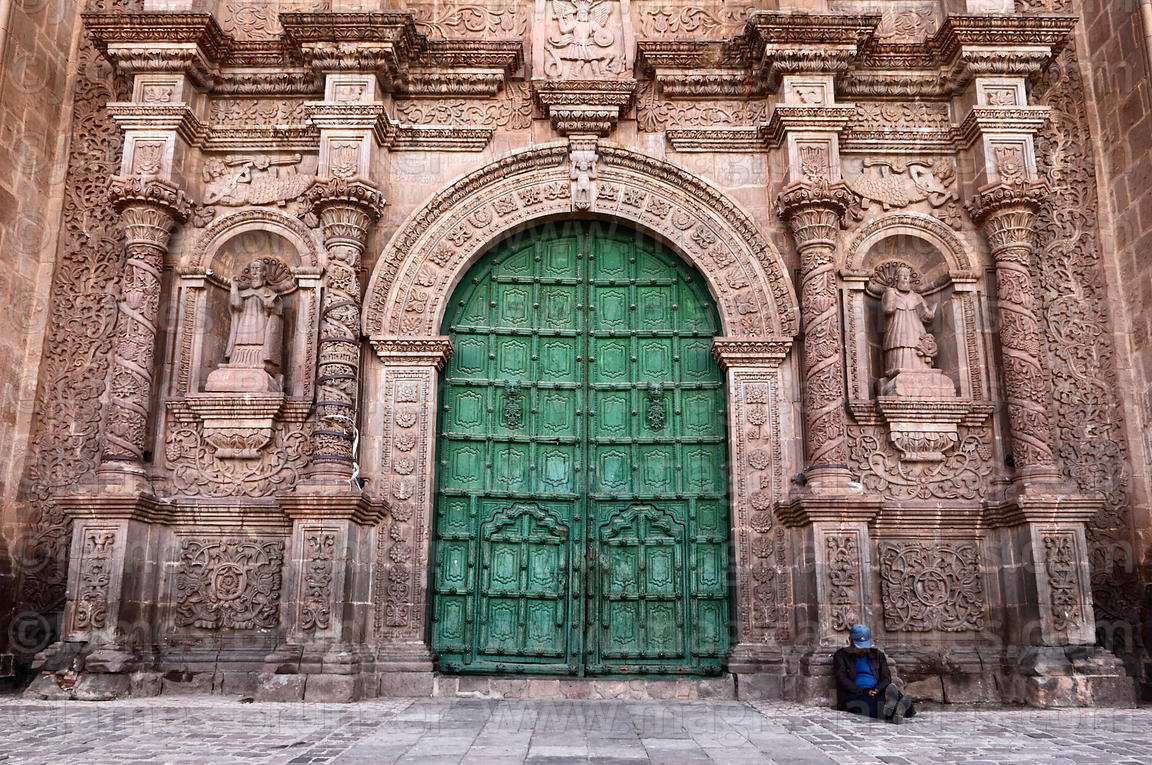 Man sitting next to main entrance of cathedral, Puno, Peru
