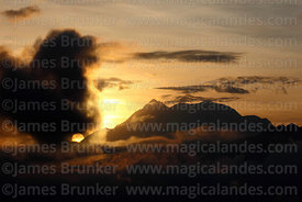 Sun rising behind cloud next to Mt Illimani, Cordillera Real, Bolivia