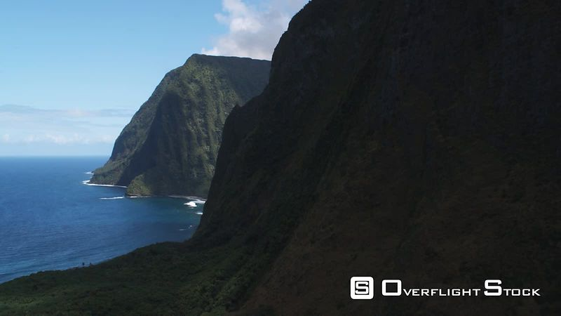 Flying past rugged cliffs to enter a valley on Molokai.