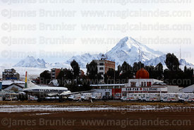 Plane outside Air Force terminal building after winter snowfall, Mt Huayna Potosí in background, El Alto, Bolivia