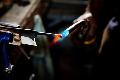 Reportage image of an artisan who hand makes knives in his riverside studio, by Douglas Kurn, photographer.