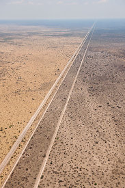 Aerial view of the results of a bushfire in the Kalahari desert, showing the road acting as a fire break, fires are normally ...