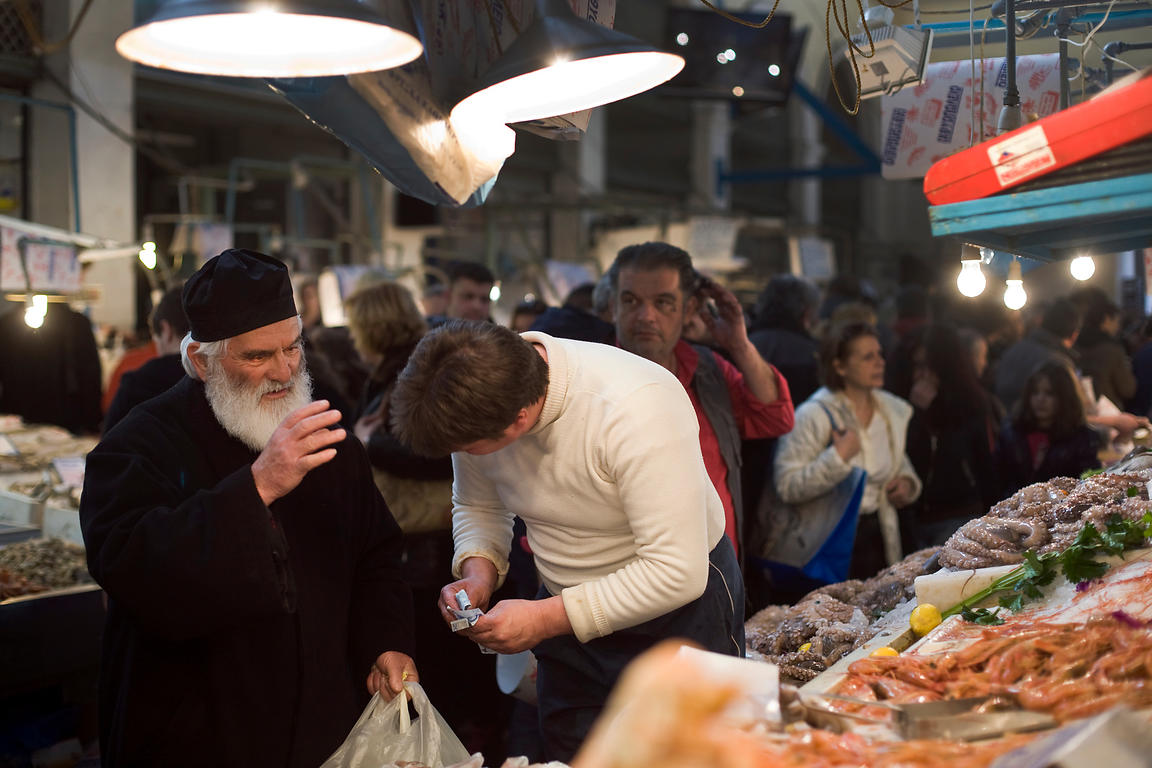 Greece - Athens - A Greek Orthodox priest blesses a fishmonger as he buys seafood from a stall in the Athens Central Market o...