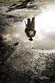 An atmospheric image of a standing, lone British soldiers, reflected in a muddy puddle in WW1.