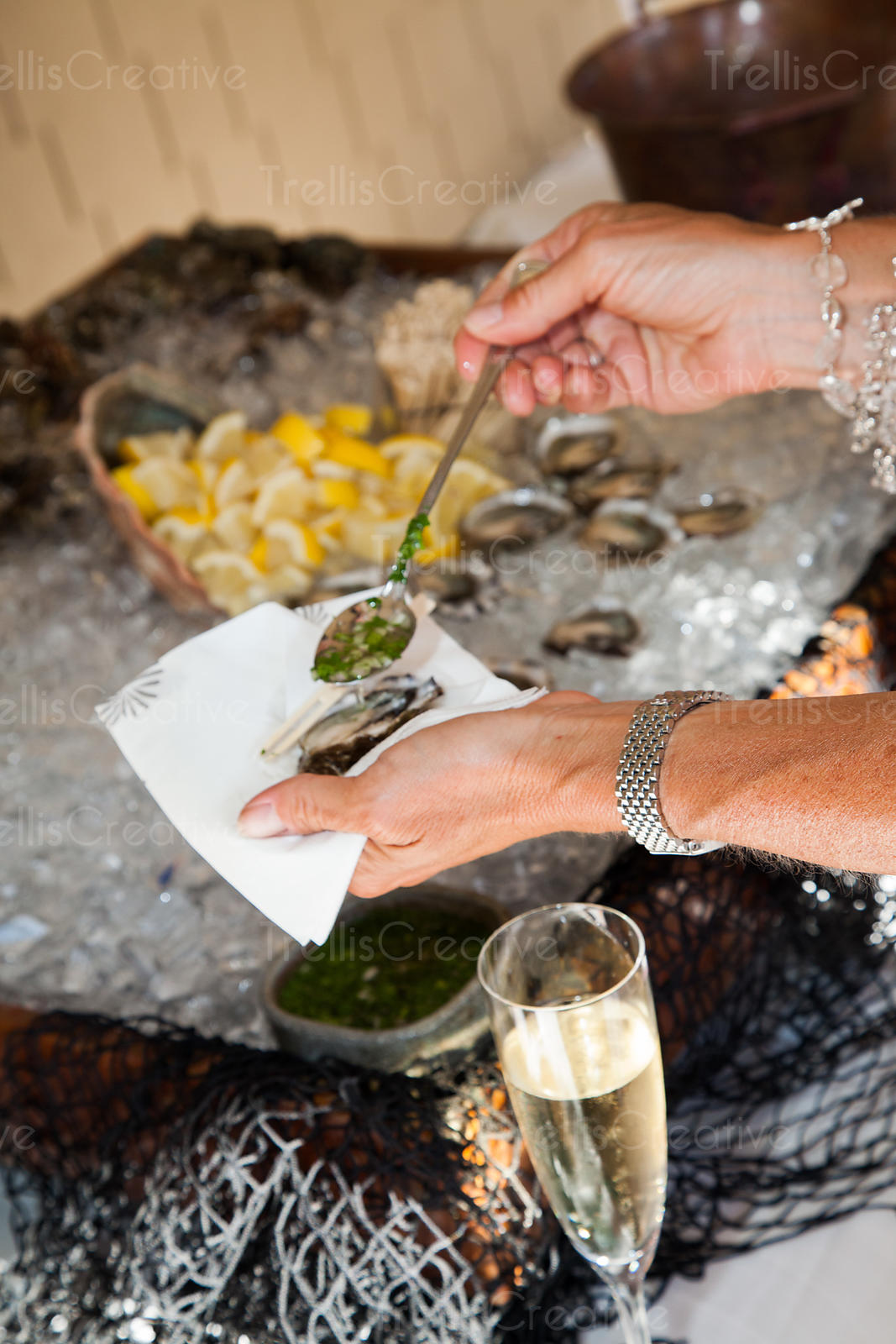 A woman spoons mignonette onto a raw oyster