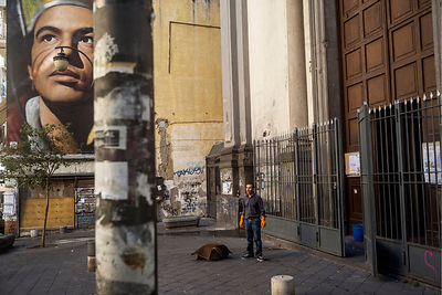 A man who has just cleaned the floors of a church stands below an enormous image of San Gennaro, the patron saint of Naples.