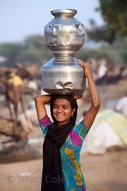 A girl carries metal pots full of water on her head at the Pushkar Camel Mela, Pushkar, India.