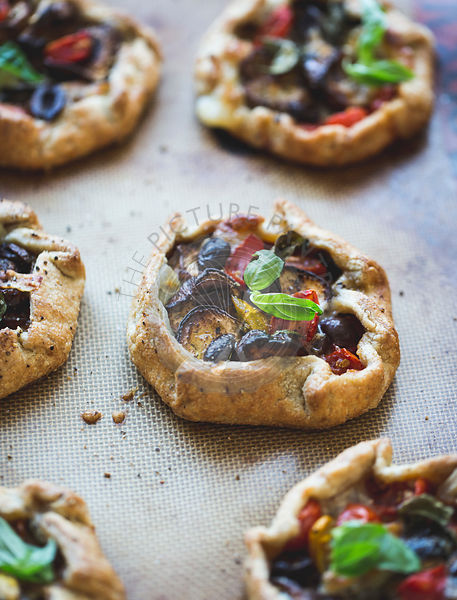 Savoury eggplant galettes with olives, tomatoes and basil.