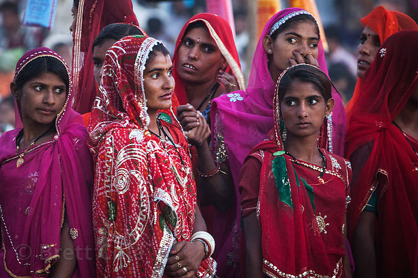Women visiting Pushkar, India watch carnival rides during the camel mela.