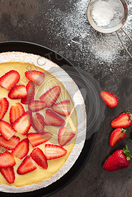 Strawberry Custard Dessert Cake with powdered sugar and ripe strawberries.