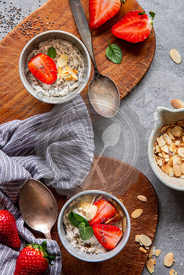 Chia pudding with strawberries, almonds and mint on brown wooden boards over grey concrete background