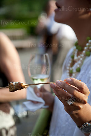 A woman eats a shishkabob with white wine