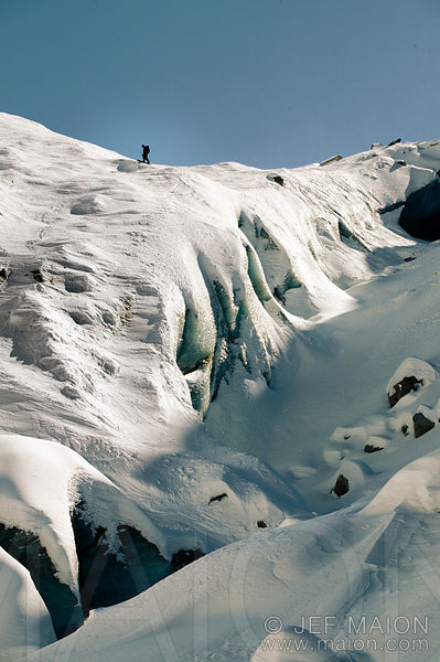 Snowboarder above vertical drop on glacier