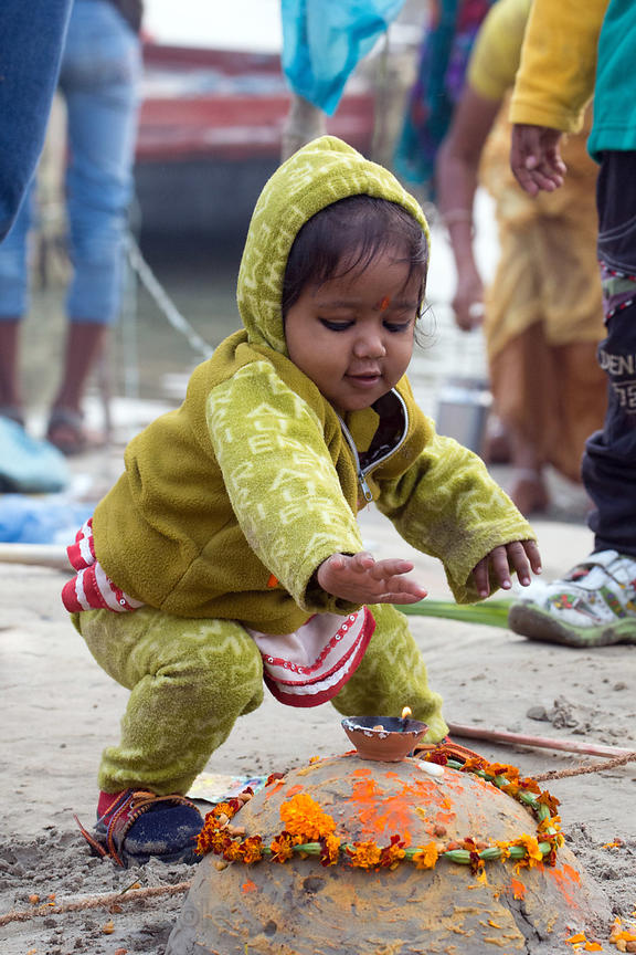 A toddler prays on the Ganges River at Assi Ghat, Varanasi, India