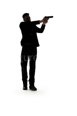 A mystery man, in silhouette, pointing a gun – shot from low level.